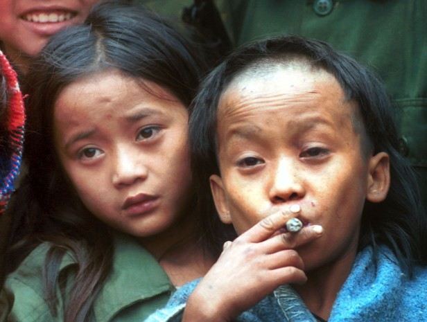 Dec. 6, 1999 - Johnny Htoo, left, watches as his twin brother Luther smokes a Myanmar cigar during a meeting with The Associated Press at their jungle base of Ka Mar Pa Law (AP Photo/Apichart Weerawong, File)